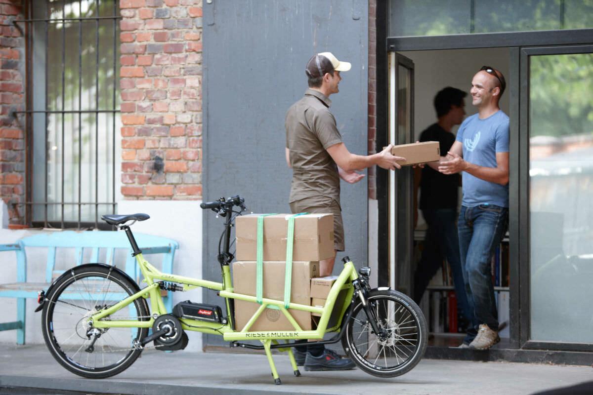 Paketbote mit Lastenrad bei der Auslieferung eines Pakets