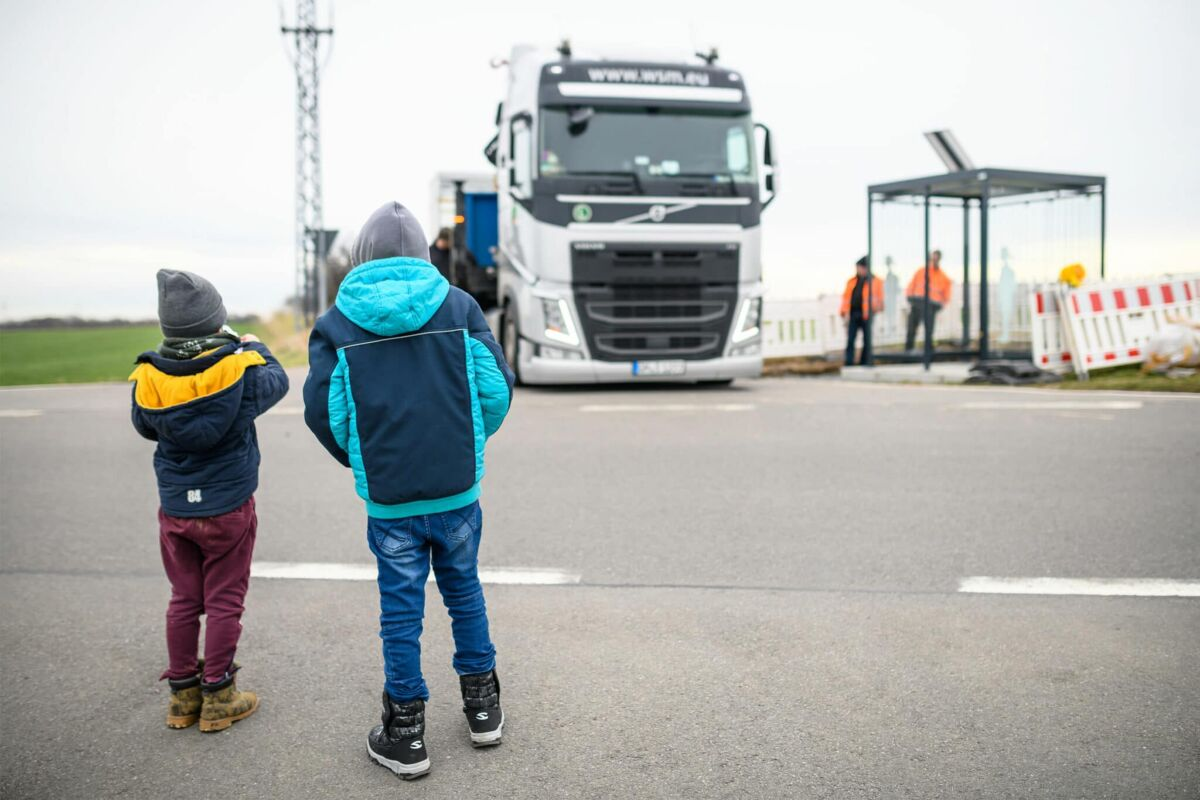 Two children observe the construction of a bus stop
